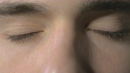 закрывать : 4k UHD - Close-up of a young man eyes opening and blinking