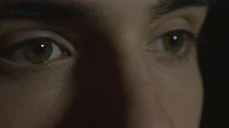 закрывать : 4k UHD - Close-up of a young man eyes in the dark