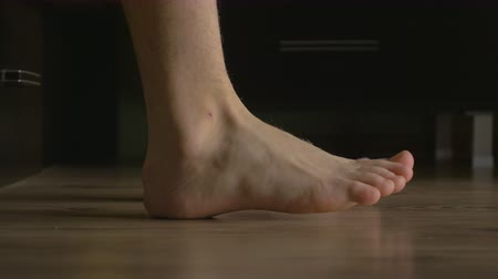 male : 4k UHD - Young male feet getting out of bed
