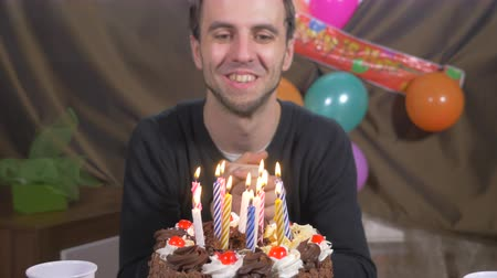 aprósütemény : 4k - Young handsome man blowing candles on a birthday cake