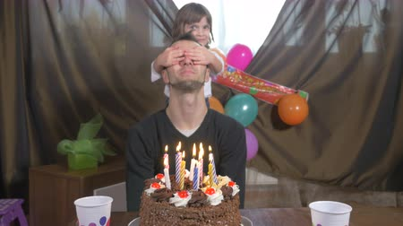 сюрприз : Young handsome man blowing candles on a birthday cake with his daughter at a surprise party