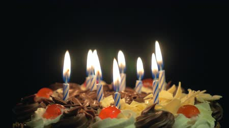 cakes : 4k - Blowing out birthday candles on a spinning delicious chocolate cake Stock Footage