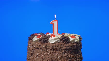 um : 4k - Blowing out number one birthday candle on a delicious chocolate cake, blue screen Stock Footage