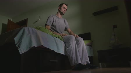 проснуться : Young handsome man waking up getting out of bed  and putting on slippers