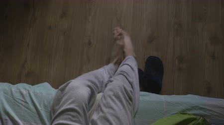 проснуться : High angle view of a handsome man waking up and putting on slippers Стоковые видеозаписи