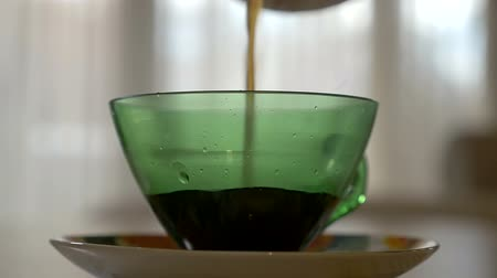 vagens : Pouring hot coffee in a transparent cup in the morning in slow motion