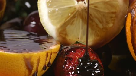 фрукты : Pouring chocolate syrup over a plate with fruit in slow motion Стоковые видеозаписи