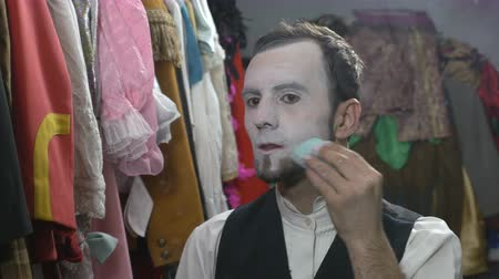 ator : Handsome young male actor applying white face cream for mime make-up