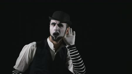 humor : Young funny mime listening to something