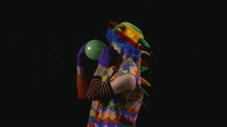 amalucado : Young funny clown inflating a balloon and balancing it on the nose Stock Footage