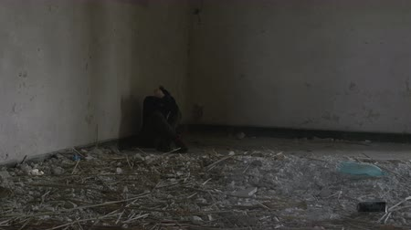 doer : Young sad abused woman sitting in an abandoned building