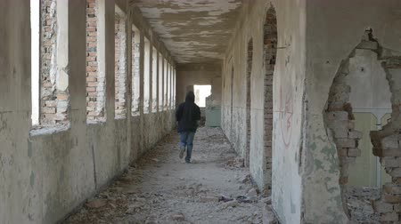 mládeži nepřístupno : Hooded frightened young man running in an abandoned military building