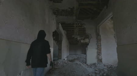 mládeži nepřístupno : Hooded young man walking through the hallway of an abandoned building