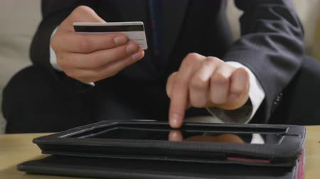 banknoty : Young businessman paying bills andusing online banking on a tablet pc
