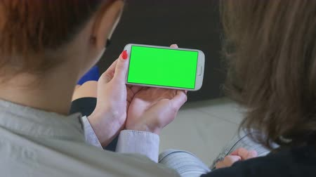 dialog : Two business women holding a smartphone with green screen