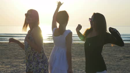 három ember : Three beautiful young women dancing on the beach at sunrise Stock mozgókép