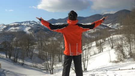 yeah : Man making arms raised victory gesture while admiring a winter landscape at the top of the mountains