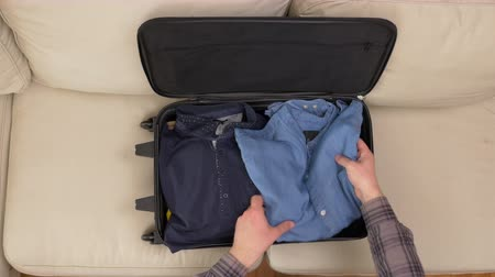 dava : Top view of male hands packing clothes and preparing suitcase for travel