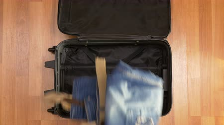 bagagem : Man hurrying up to pack clothes into travel suitcase