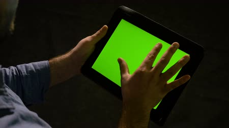 trabalhar fora : Man using tablet pc with green screen and zooming in and out on the display