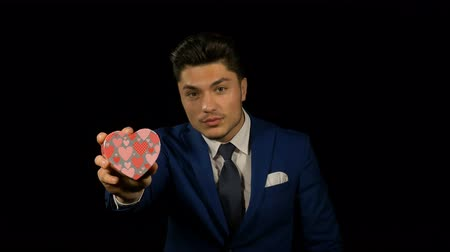 heart shaped : Young man holding heart shaped cardboard box with red heart inside as a gift