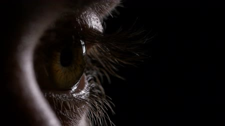 dilated pupil : Macro of young man eye opening and blinking in the dark Stock Footage