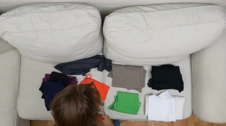 аккуратный : Top view of girl choosing and folding clothes ready for summer holiday