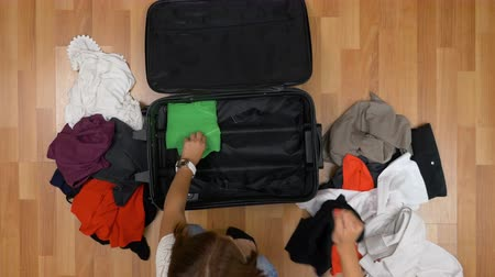 levou : Top view of young girl sitting on wooden floor and unpacking clothes from trolley bag