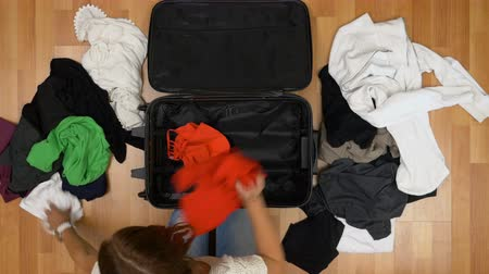 bagagem : Top view of woman throwing clothes into a suitcase closing and leaving in a hurry