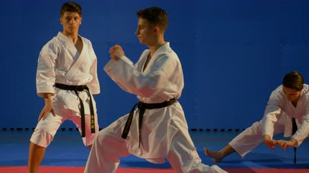каратэ : Three teenagers doing warm up before martial arts competition