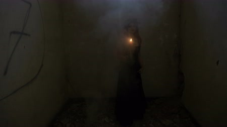 bewitch : Gothic dressed vampire woman holding a candle turning around in a smoky abandoned house