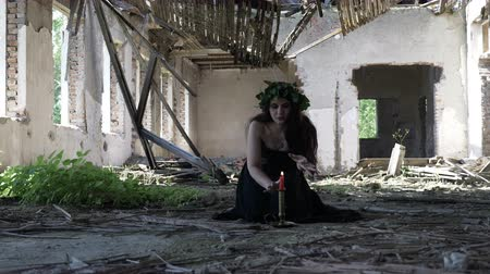 wicca : Beautiful witch conjuring and invoking maleficent spirits with incantation and candles in an abandoned ruined mansion Stock Footage