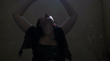 perverso : Black magic witch possessed by a demon laughing and raising hands calling dark spirits