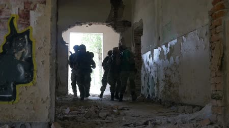 süzülme : Slow motion of special infiltration unit walking to an entrance of an abandoned building searching enemy