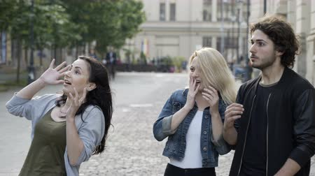 csodálkozás : Group of three friends walking on street expressing surprise with hand gesture and mouth opened seeing something scary Stock mozgókép