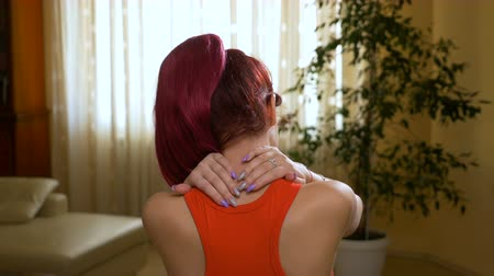 pained : Young pained woman massaging her back of neck to heal the pain at home