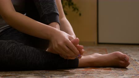 pained : Closeup of barefoot young woman massaging her sprained foot having painful symptoms