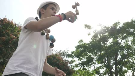 ügyesség : Closeup of teenage kendama toy collector exercising tricks outdoor in slow motion Stock mozgókép