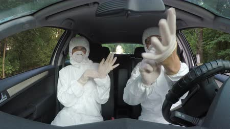 hazmat : Funny hazmat scientist workers in car dancing and putting on gloves and suit preparing for investigation