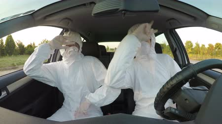 energized : Young funny scientists sitting in car dressed in hazmat wear dancing and feeling energized and celebrating achievement Stock Footage