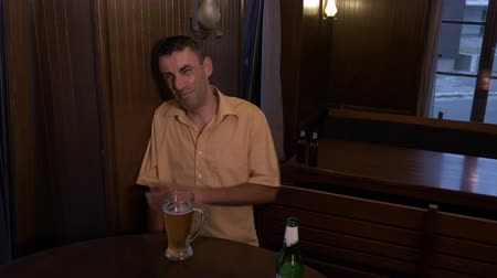 wasted : Drunk guy sitting a table in a pub cannot hold his glass with beer