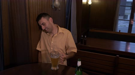 wasted : Drunk guy sitting at a table in a pub and drinking beer