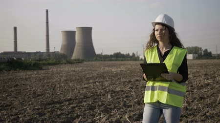 charged : Young engineer woman in charge with work safety inspecting on site construction taking notes about industrial activity