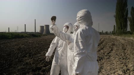 bacteriological : Biologists workers in hazmat clothing looking at contaminated piece of soil earth from an agricultural field in the of refinery