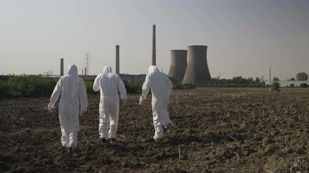 bacteriological : Scientists dressed in hazmat suits carefully walking across a contaminated field near a power plant Stock Footage