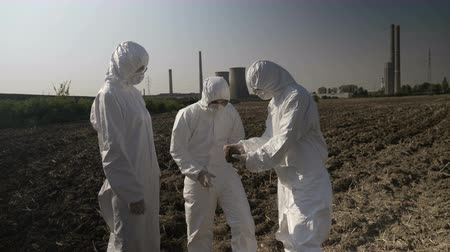 bacteriological : Technical team of lab employees in hazmat suits sampling and examining vegetation and soil from field near of power plant Stock Footage