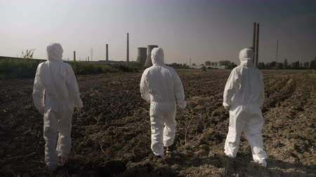 bacteriological : Employees ecologists team in hazmat suits looking at contaminated environment and agricultural area walking towards a nuclear power refinery