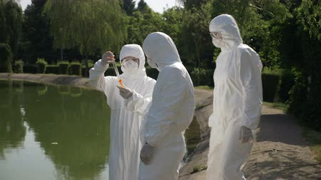 bacteriological : Hazmat technicians team taking infected water sample in a park and examining it near contaminated lake
