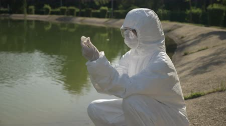 bacteriological : Hazmat biologist injecting a catalyst in a polluted water sample examining the chemical effect Stock Footage