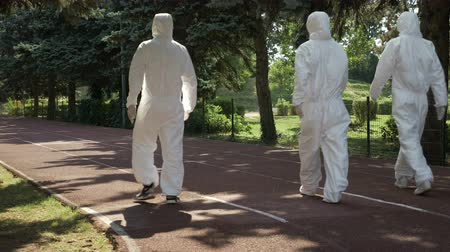 bacteriological : Hazmat technicians team walking on a an alley in public park toward contaminated area